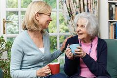Woman Taking Time To Visit Senior Female Neighbor And Talk Stock Photos