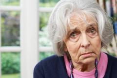 Head And Shoulders Portrait Of Unhappy Senior Woman At Home - stock photo