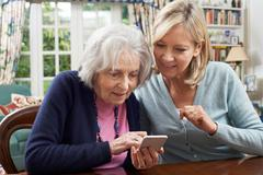 Woman Helping Semior Neighbor To Use Mobile Phone Stock Photos