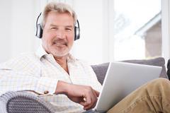 Mature Man Streams Music From Laptop To Wireless Headphones - stock photo