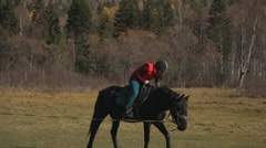 The woman is leaning back and forward touching stirrup learning to ride a horse Stock Footage