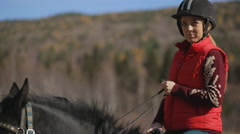 The woman jockey is sitting on horse with harness and bridle Stock Footage