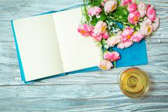 notepad, white wine and flowers - stock photo