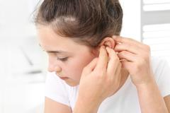 The girl assumes hearing aid. Stock Photos