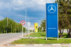 Official dealership sign of Mercedes-Benz in summer sunny day - stock photo