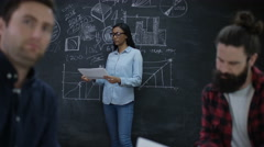 4K Professional team in business startup. Focus on woman looking at blackboard Stock Footage