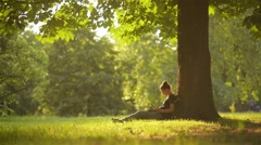 Young woman student using digital tablet for studying while sitting in the park Stock Footage