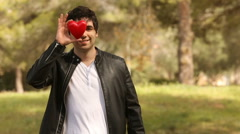 Young man covering his face with a heart shape Stock Footage