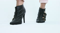 Woman posing in black leather heels on a white background Stock Footage