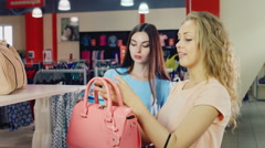 Two young women choose their handbags in the store Stock Footage