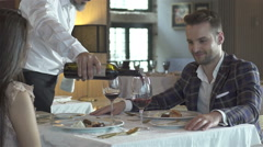 A couple on an intimate dinner. Waiter serving them wine. - stock footage