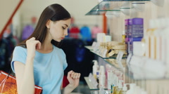 Attractive brunette chooses liquid soap in a perfume shop Stock Footage