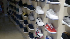 Sports footwear sneakers on shelves of fashionable shopping clothes store Stock Footage