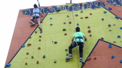 Children are engaged in practicing rock climbing on the climbing gym Stock Footage