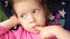 Little girl child sucks a finger - she put into a mouth her dirty hands Stock Footage