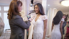 4K Beautiful bride to be trying on wedding gown in store with sales assistant Stock Footage