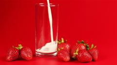 Milk is poured into a glass and around scattered strawberry on red background - stock footage
