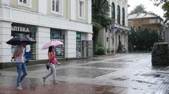 People couple walk under umbrellas in the rain walking down the street - stock footage