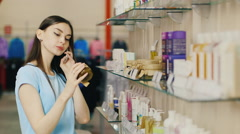 Young woman chooses items in the perfume department, talking on the phone Stock Footage