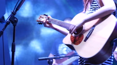 Singer girl during a concert playing an acoustic guitar - stock footage
