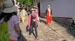 China group Chinese women tourists in colorful clothes walking in old city tour - stock footage
