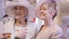 4K 2 Mature ladies drinking champagne & trying on clothing for a special event.  Stock Footage