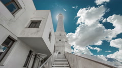 White Tower of the mosque before the sun on a background of blue sky and clouds Stock Footage