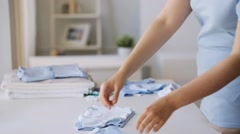 Pregnant woman folding baby boys clothes at home Stock Footage