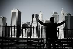 Man with arms open and view of lower manhattan - stock photo