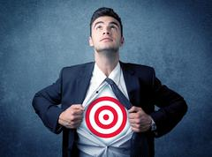 Businessman tearing shirt with target sign on his chest - stock photo