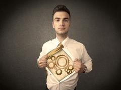 Businessman tearing shirt off and machine cog wheel shows - stock photo
