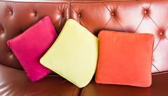 Cozy sofa with pillows. Living room interior and home decor concept Stock Photos