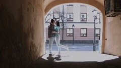 Cute girl and boy with long hair in dark glasses kissing in the alley Stock Footage