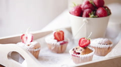 Tasty cakes (muffins) with fresh strawberries on the wooden tray sugar powdered Stock Footage