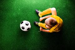 Unrecognizable little football player against green grass, studi - stock photo