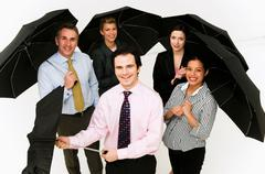 Group of business people with umbrellas Stock Photos