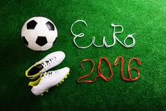 Soccer ball, cleats and Euro 2016 sign against artificial turf Stock Photos