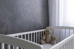 a teddy bear sitting in a crib - stock photo