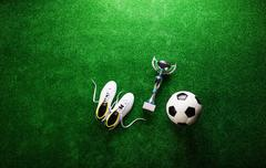 Soccer ball, cleats and trophy against green artificial turf Stock Photos
