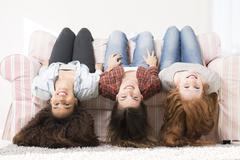 three happy young woman laying on a sofa with their heads down - stock photo