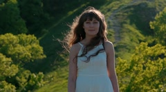 young beautiful brunette woman in a white dress looking and smiling on nature - stock footage