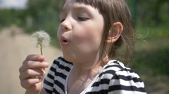 girl blowing on a dandelion and smiling close up slow motion - stock footage