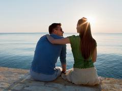 Couple by sea watching sun set Kuvituskuvat