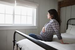 Expectant mother sitting on bed - stock photo