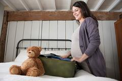 Expectant mother packing suitcase - stock photo