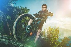 Extreme Bike Ride Sport. Caucasian Biker on His Mountain Bike Riding Stock Photos