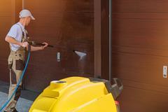 Garage Door Washing by High Pressured Water. Caucasian Men Cleaning Garage Stock Photos