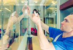 Glassy Office Interior Cleaning. Caucasian Men Cleaning Glass Elements. Stock Photos