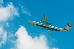 Turboprop Jet Airplane Traveling. Airplane on the Cloudy Blue Sky. - stock photo