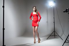 Young model in red dress posing in spotlight - stock photo